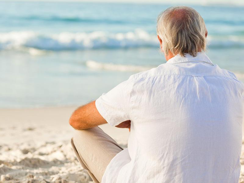 Homme retraité assis devant la mer.
