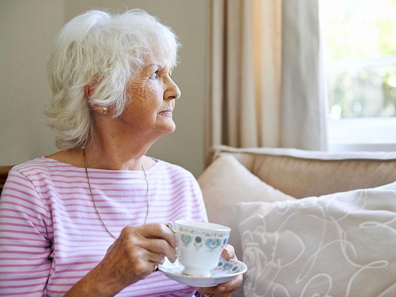 Femme âgée pensive, tenant une tasse de thé et regardant par la fenêtre.