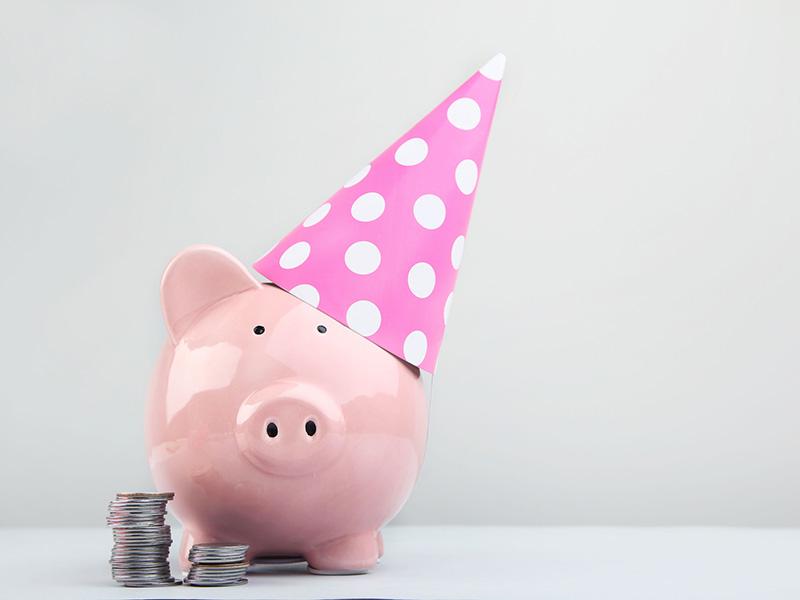 Tirelire en forme de cochon portant un chapeau de fête.
