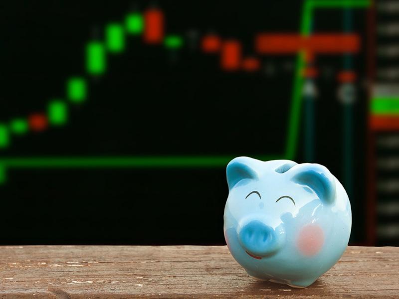 Tirelire bleue devant un écran présentant les cours de la Bourse.
