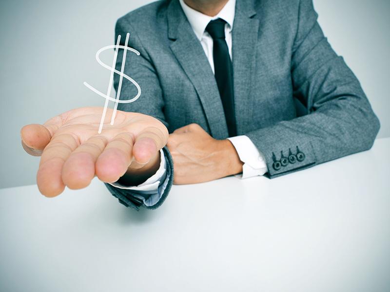 Homme d'affaires tendant une main contenant un signe de dollar.