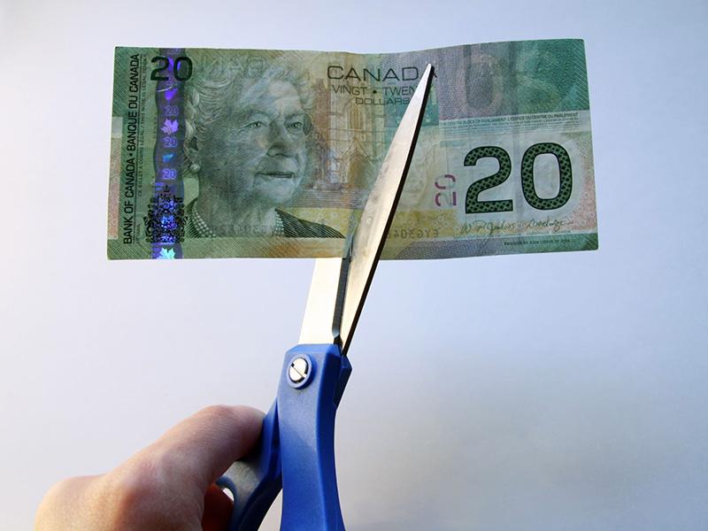 Billet de 20 dollars canadiens coupé en deux avec des ciseaux.