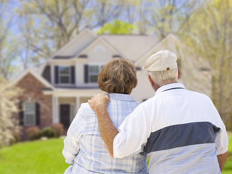 Couple de retraités devant leur maison.