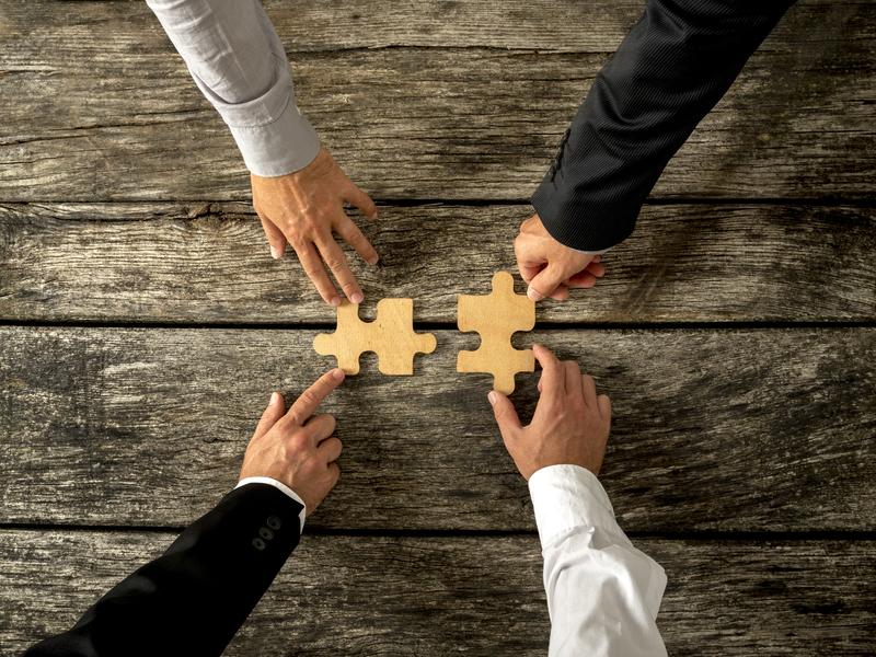 Quatre mains appartenant à des hommes d'affaires poussent des morceaux de casse-tête l'un vers l'autre pour les unir.