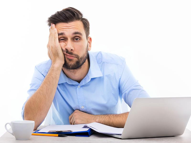 Homme exprimant un air d'ennui devant son ordinateur.