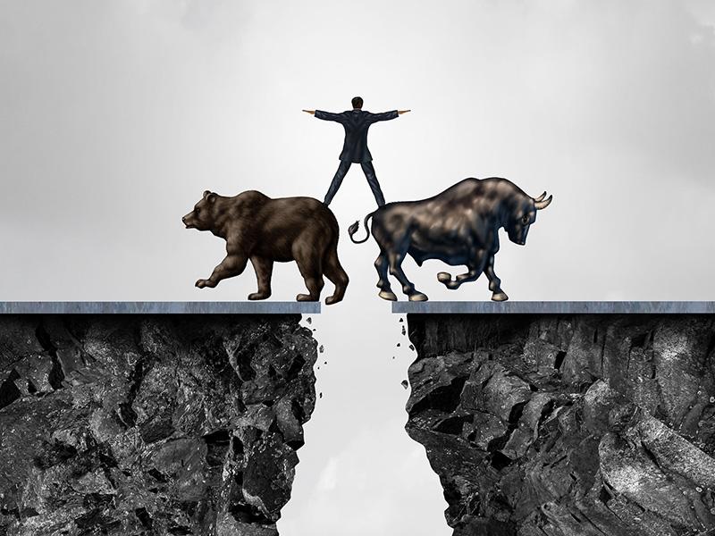 Homme d'affaires en équilibre debout sur un ours et un taureau, au-dessus d'un ravin.