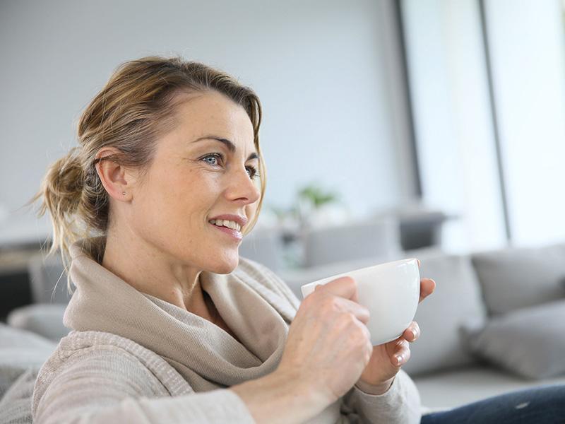Femme pensive, tenant une tasse de café.