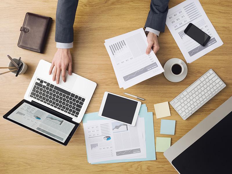 Bureau de travail avec ordinateur, tablette et paperasse.
