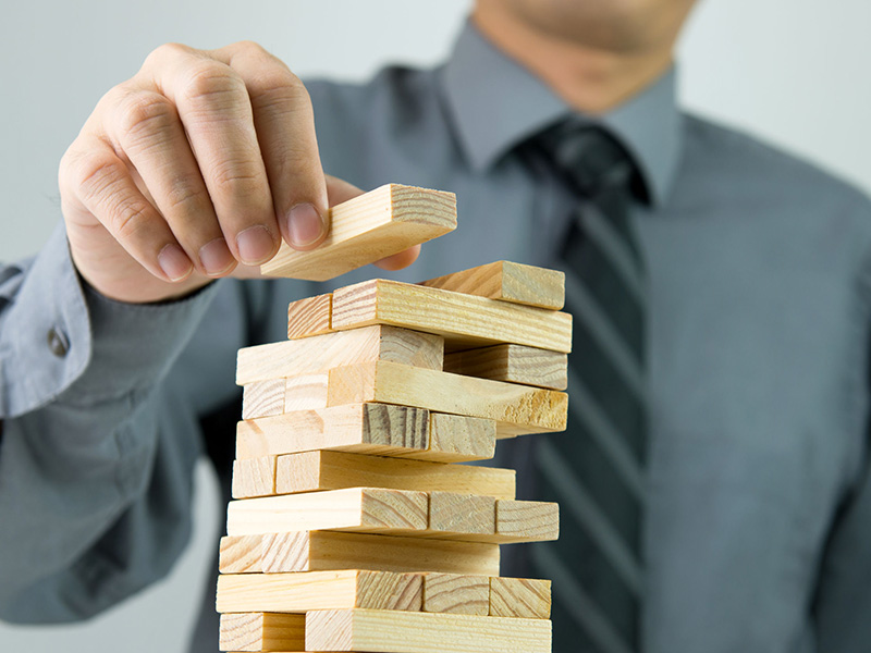 Homme d'affaires déposant un bloc de bois sur un jeu de Jenga.