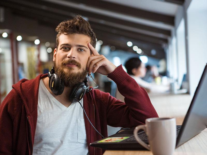 Jeune homme confiance, avec barbe et écouteurs, assis devant son ordinateur portable.
