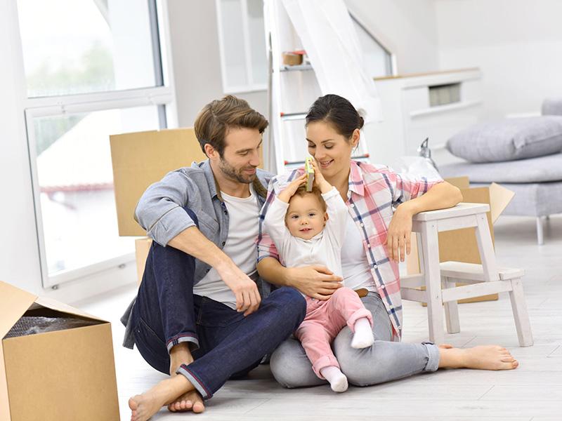 Jeune couple et leur bébé dans leur nouvelle maison, entourés de boîtes.