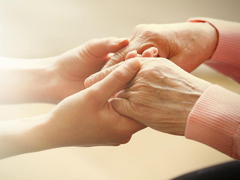 De jeunes mains de femmes tiennent celles d'une femme âgée.