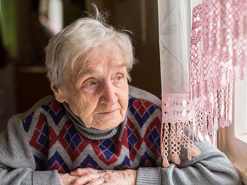 Femme âgée pensive, assise au bord d'une fenêtre.