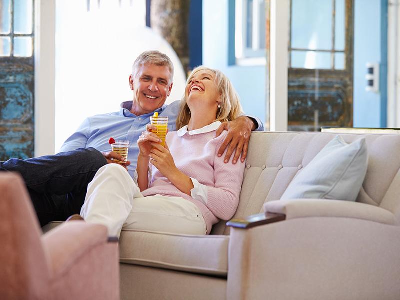 Couple de retraités assis sur un canapé.