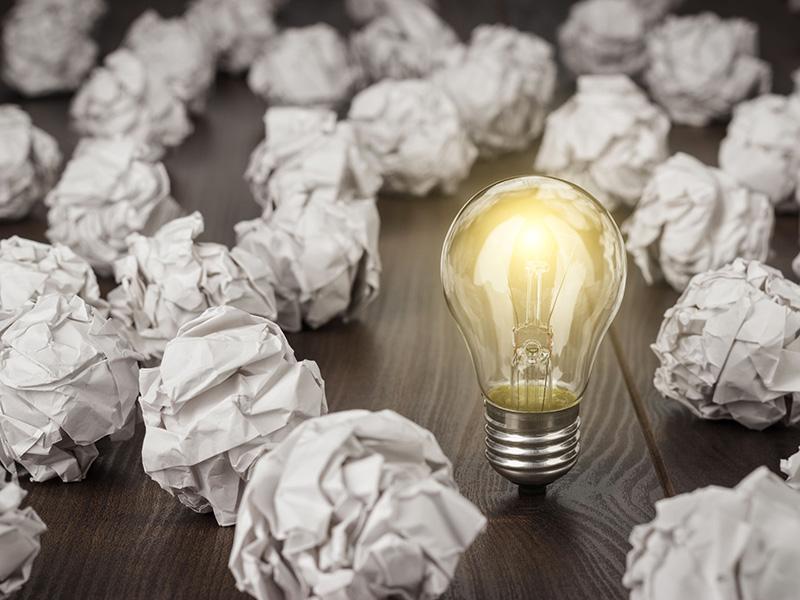 Ampoule électrique allumée parmi des boules de papier.