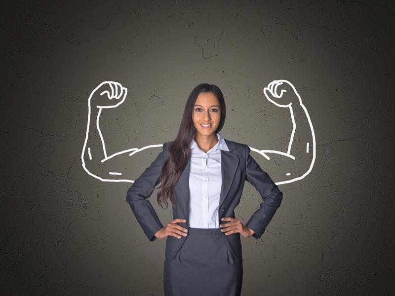 Une femme d'affaire fière. Derrière elle, on voit des bras musclés dessinés à la craie sur un tableau noire.