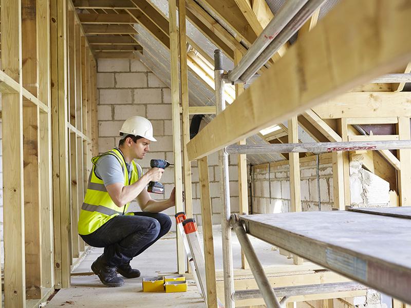 Employé de la construction s'affairant sur une structure.