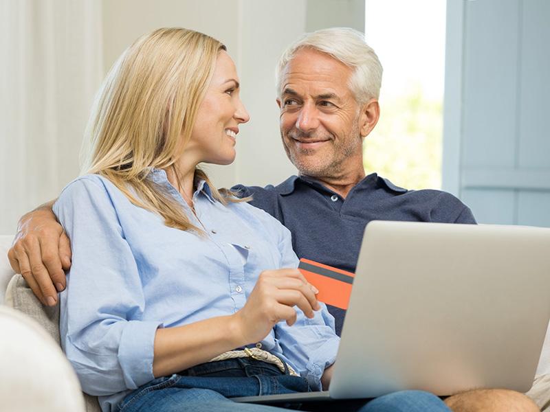 Couple retraité discutant devant un ordinateur portable.