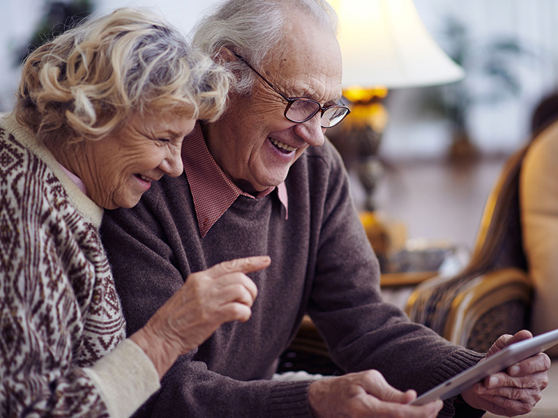 Couple retraité s'amusant à regarder une tablette.
