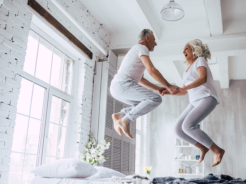 Couple de retraités sautant dans un lit.