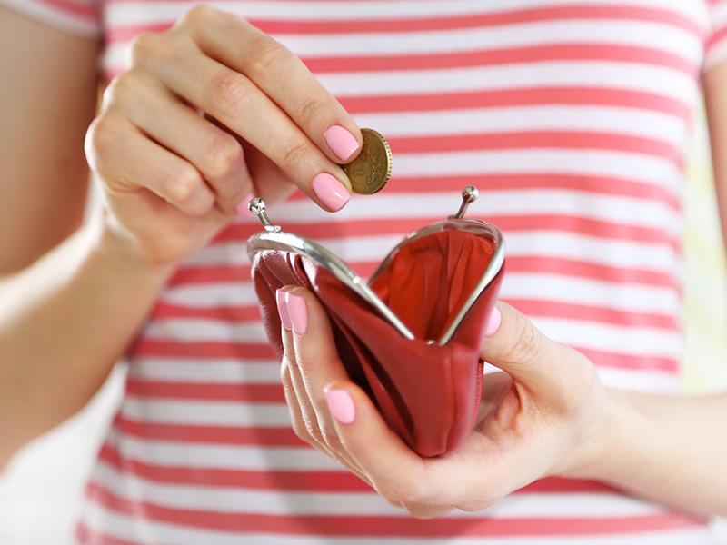 Femme déposant une pièce de monnaie dans un portefeuille.