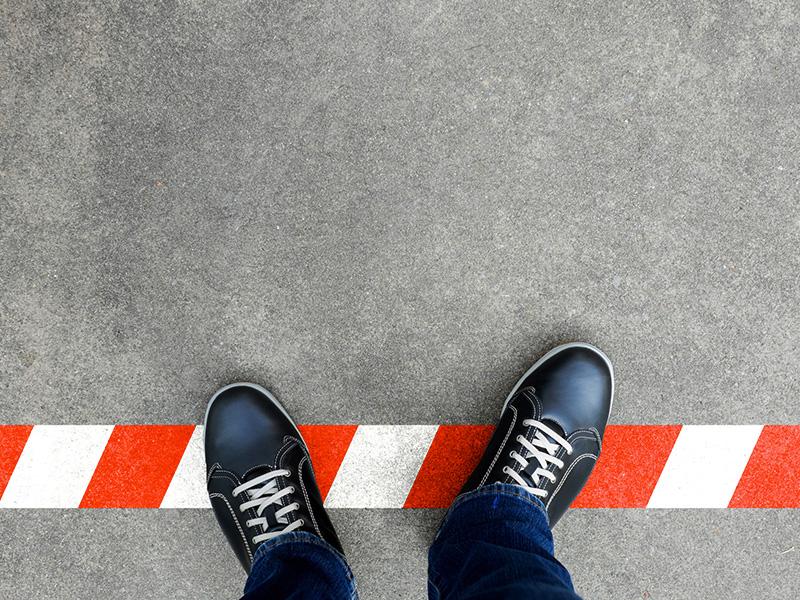 Pieds franchissant une limite peinte sur la chaussée.