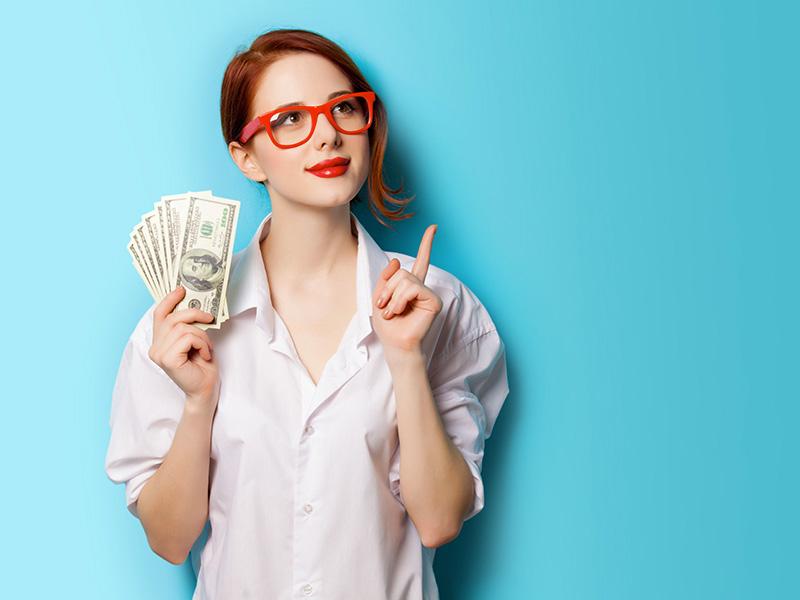 Femme rousse astucieuse tenant des billets de banque.