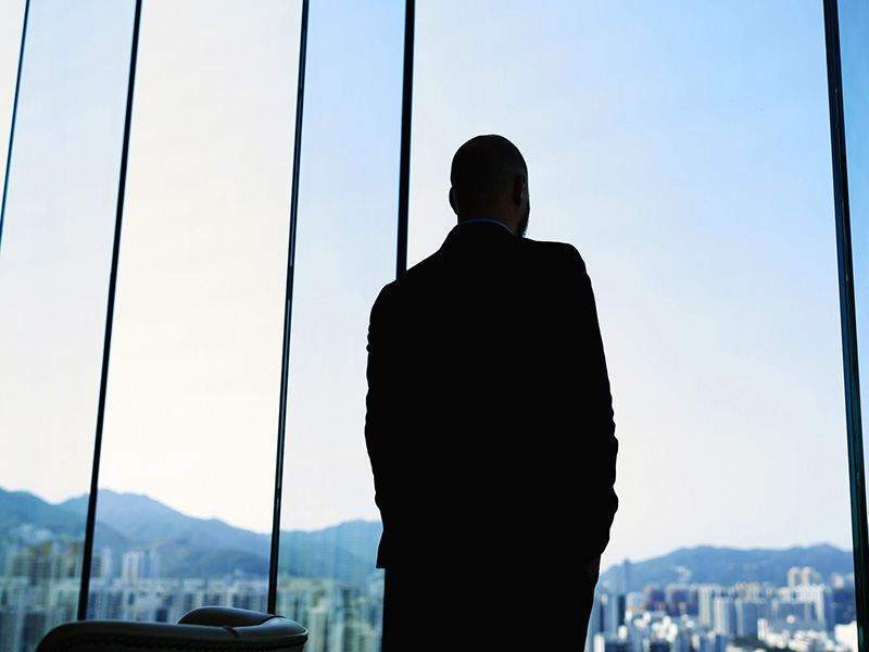 Homme d'affaires devant une fenêtre, en contre-jour.