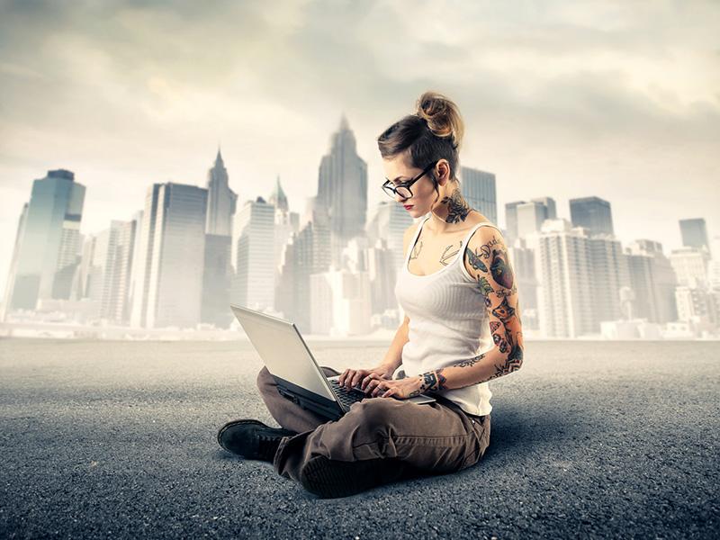 Jeune femme avec tatouages, assise par terre et travaillant sur un ordinateur portable.