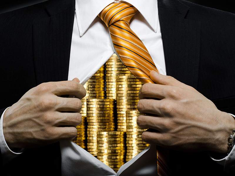 Pièces d'or cachées dans la chemise ouverte d'un homme d'affaires.