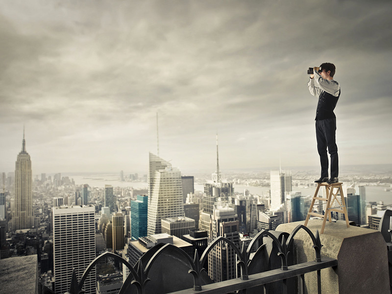 Homme d'affaires observant la ville avec des jumelles, du haut d'un gratte-ciel.