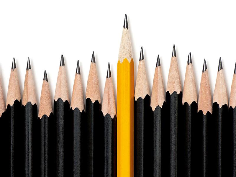 Rangée de crayons à mine noirs, un crayon à mine jaune sortant du lot.