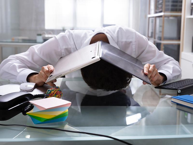 Employé se cachant sous un cartable, assis à son bureau.