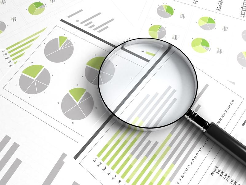 Loupe sur des documents montrant graphiques et tableaux illustrant des données financières