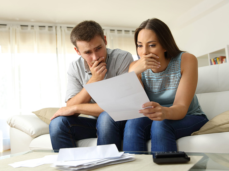 Jeune couple inquiet, examinant des documents.