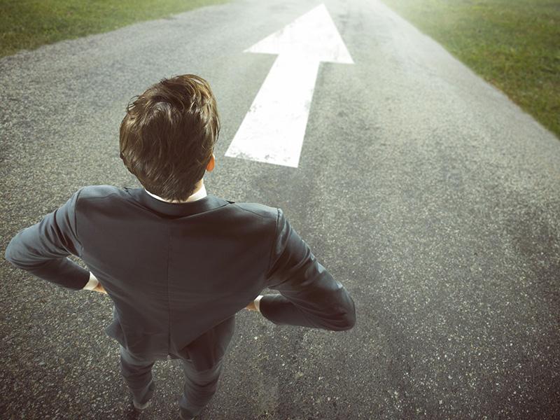 Homme d'affaires se tenant debout, face à une flèche indiquant une direction à suivre.