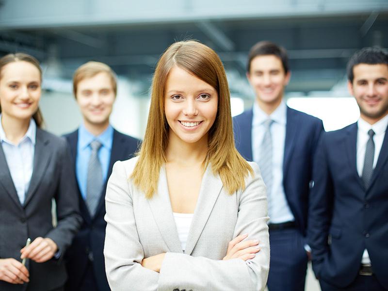 Un groupe d'hommes et de femmes d'affaires, avec, au centre, une jeune femme affichant un air confiant.