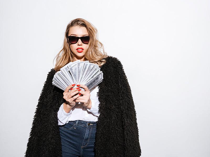 Jeune femme portant des verres fumés et tenant des billets de banque.