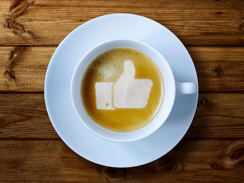 Café au lait avec dessin de pouce vers le haut formé dans la mousse.