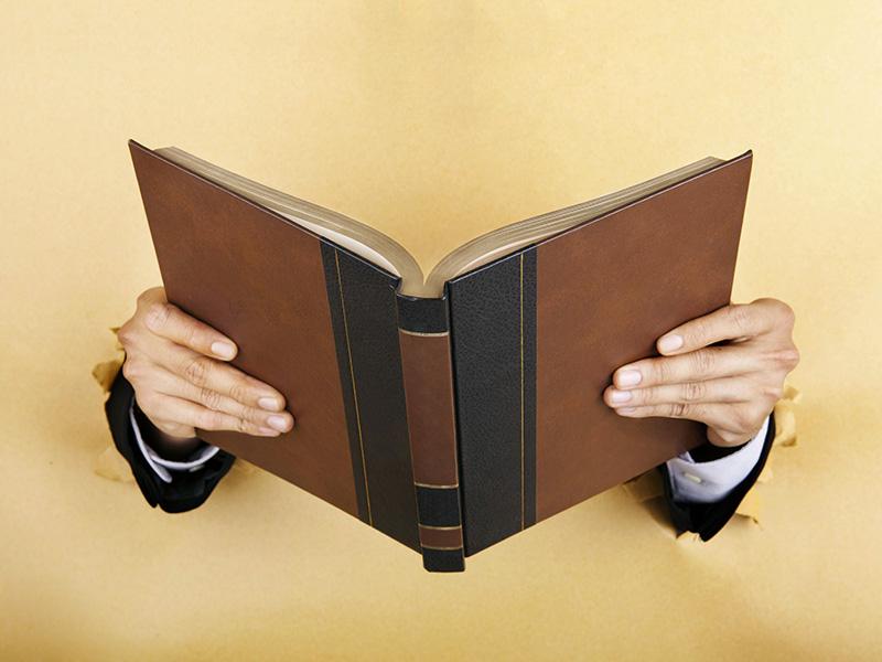 Livre tenu par des mains émergeant d'un mur.