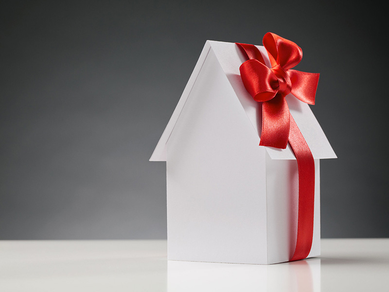 Petite maison blanche en papier, avec une boucle rouge.