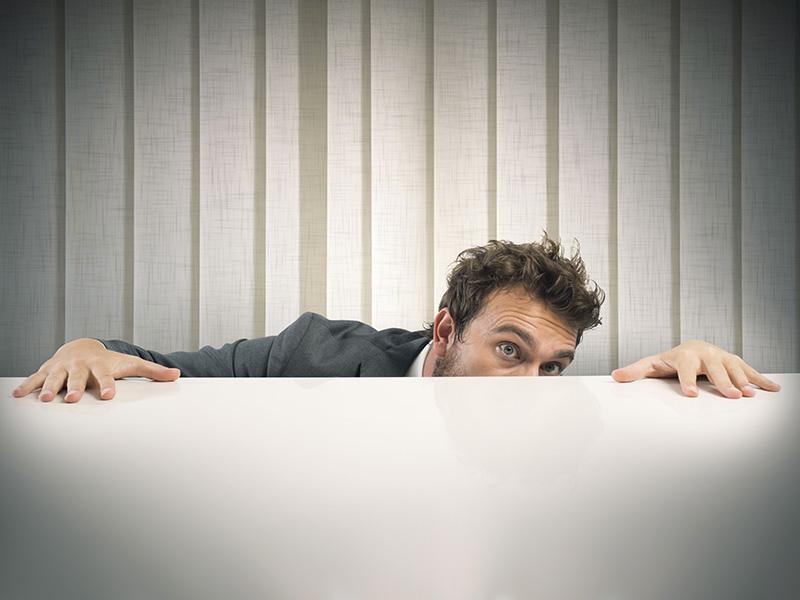 Conseiller se cachant derrière son bureau.