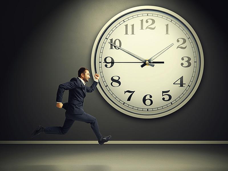 Homme d'affaires courant devant une immense horloge.