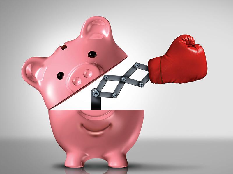 Un gant de boxe émergeant d'une tirelire en forme de cochon