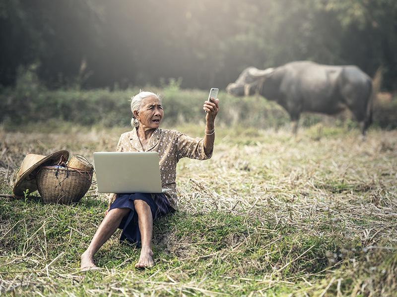 Femme âgée vietnamienne assise dans un champ et prenant un selfie.