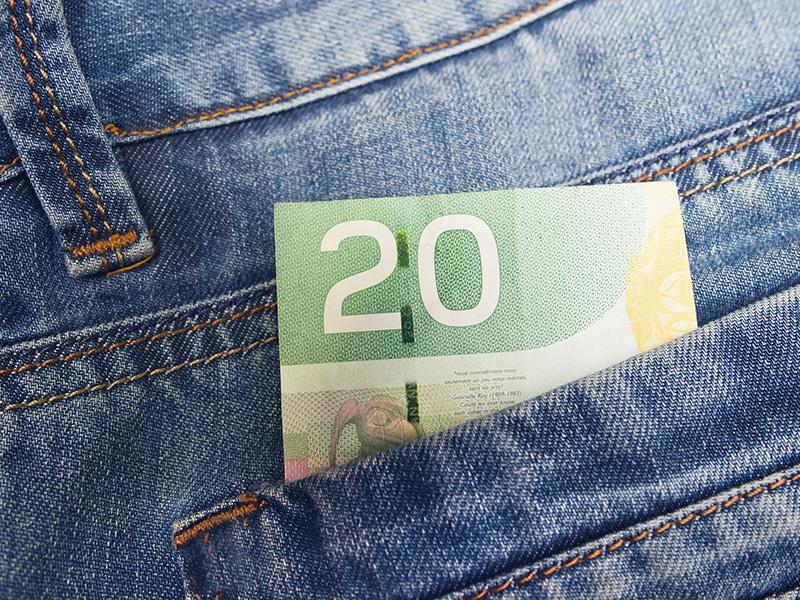 Billet de 20 $ canadiens glissé dans une poche de jeans.