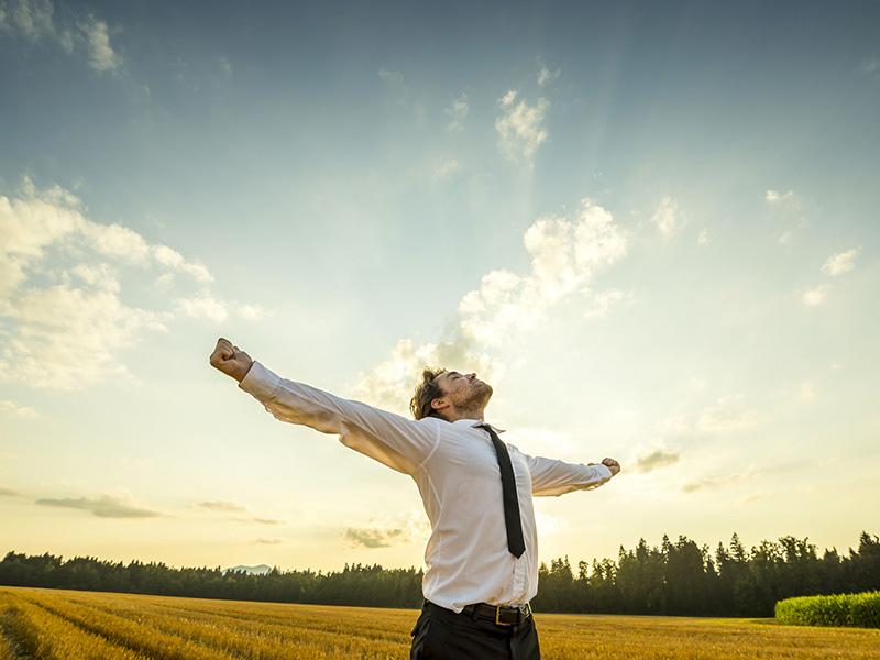 Homme d'affaires dans un champ de blé, levant les bras vers le ciel.