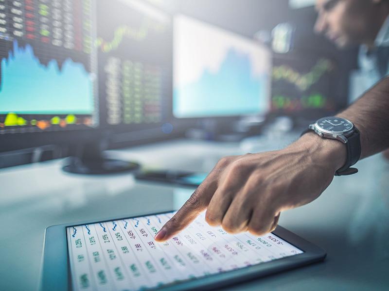 Main pointant une tablette, devant des écrans d'ordinateur affichant des courbes de rendement.
