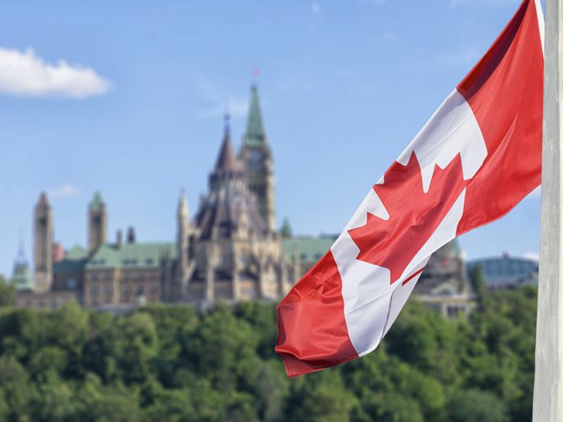 Drapeau du canada flottant devant le parlement, à Ottawa.
