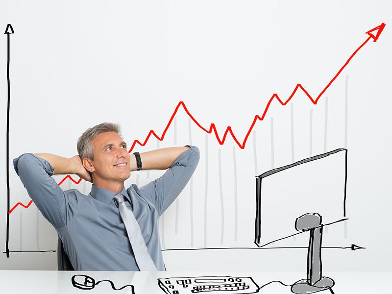 Conseiller heureux, assis à son bureau, les bras croisés derrière la tête, la courbe positive d'un rendement affichée derrière lui.